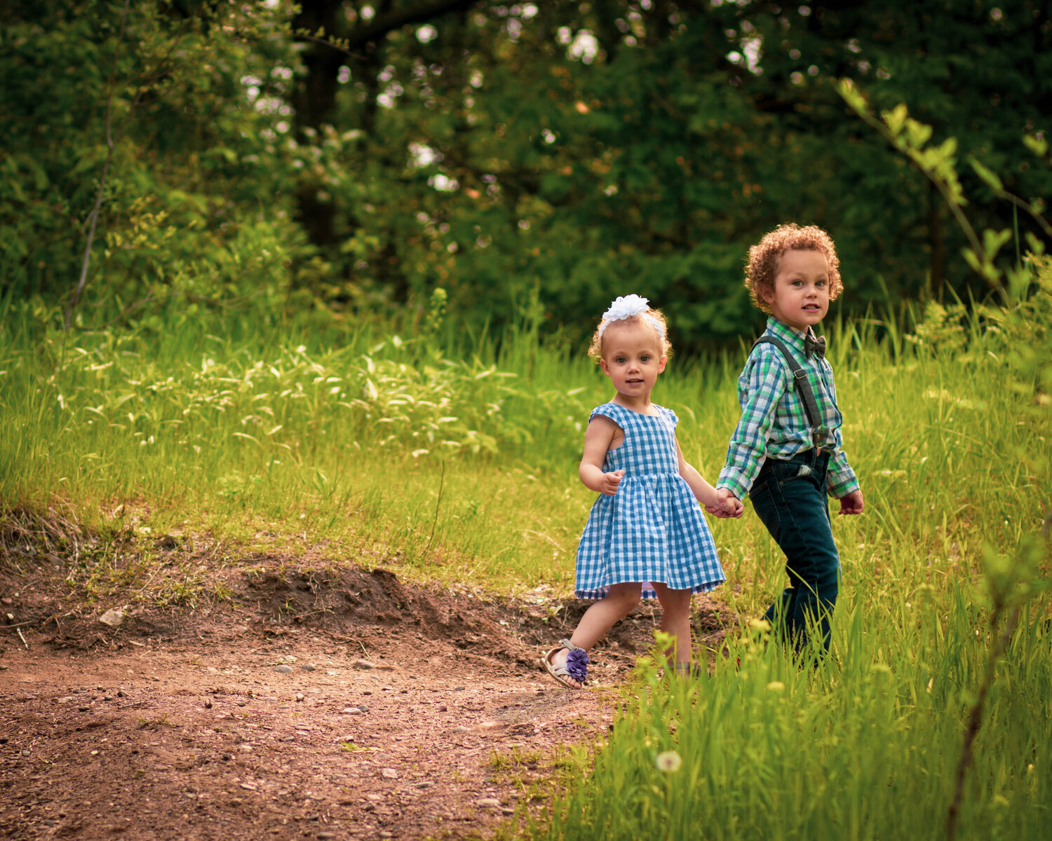 brother and sister holding hands on hiking trail in Woodbury MN