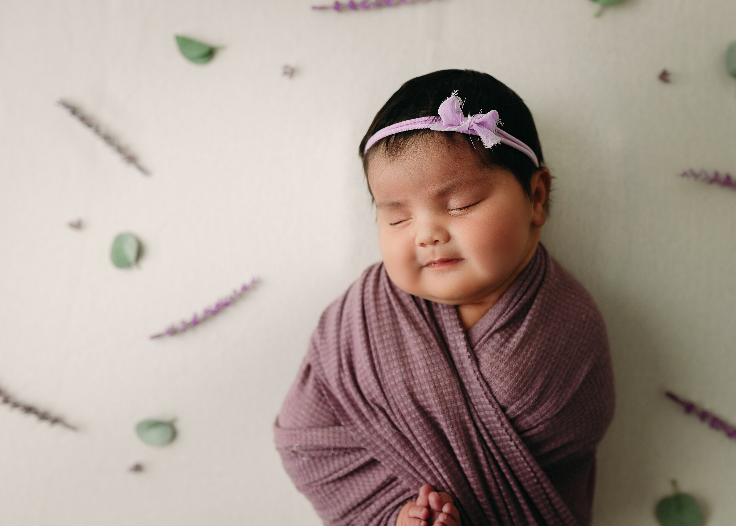 baby girl in lavendar on cream backdrop with lavender branches and leaves for minneapolis newborn photographer session