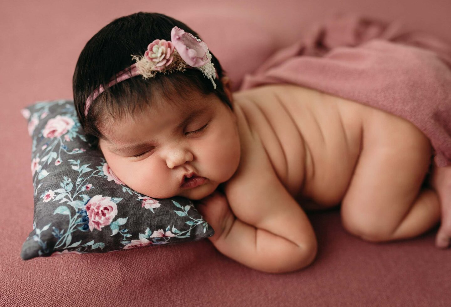 baby girl in pink and teal floral on mauve backdrop for minneapolis newborn session