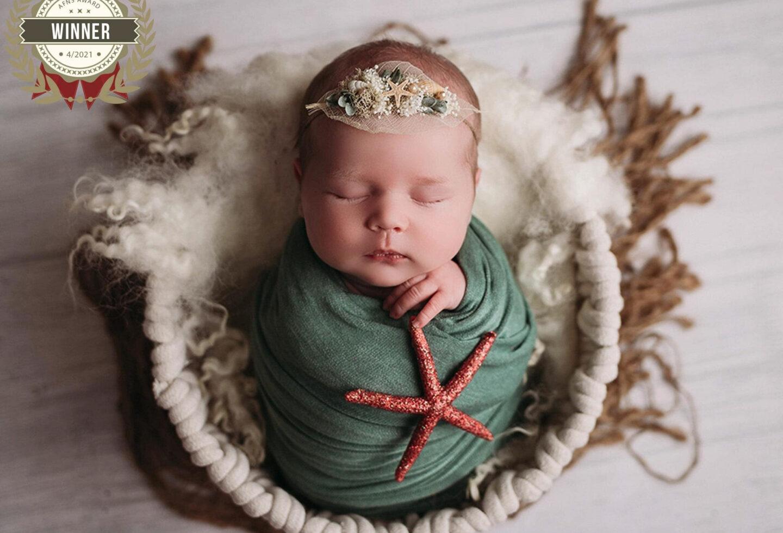 newborn baby girl in starfish headband in minneapolis mn