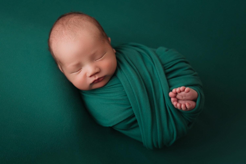 newborn baby on emerald green in minneapolis mn
