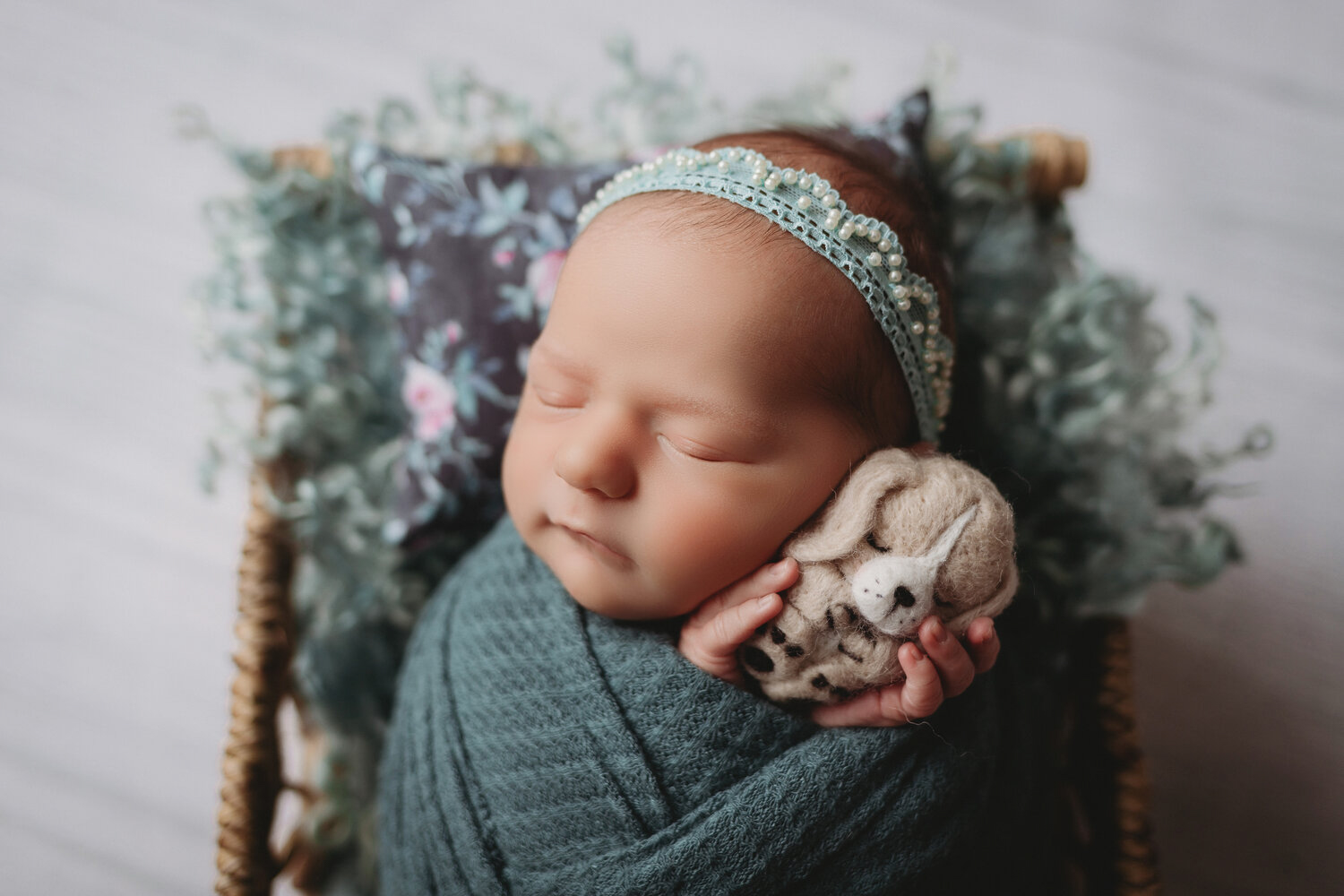 baby girl in teal and pearls with puppy for newborn photography session in minneapolis mn