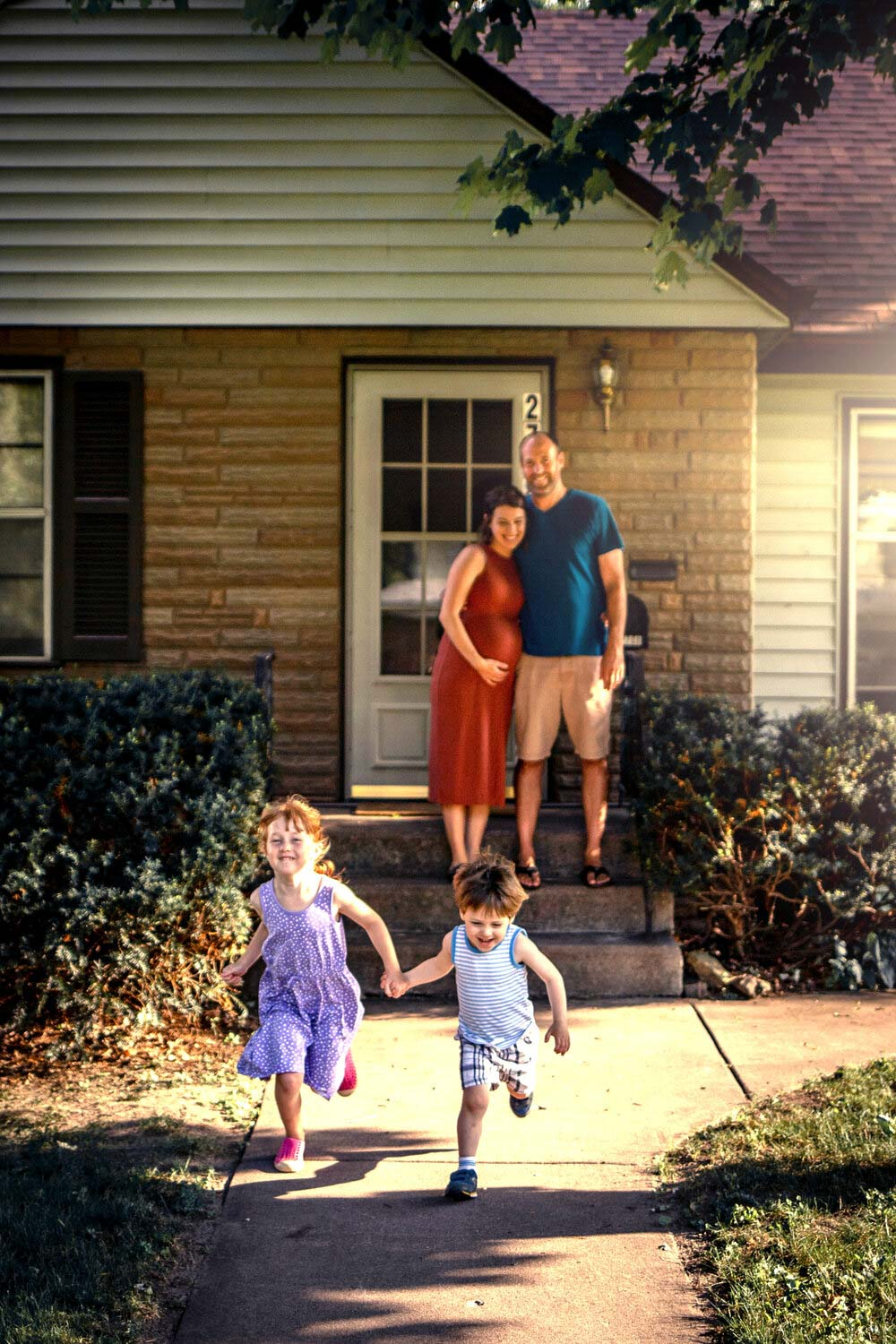 front step maternity photography with two kids at golden hour in st anthony village
