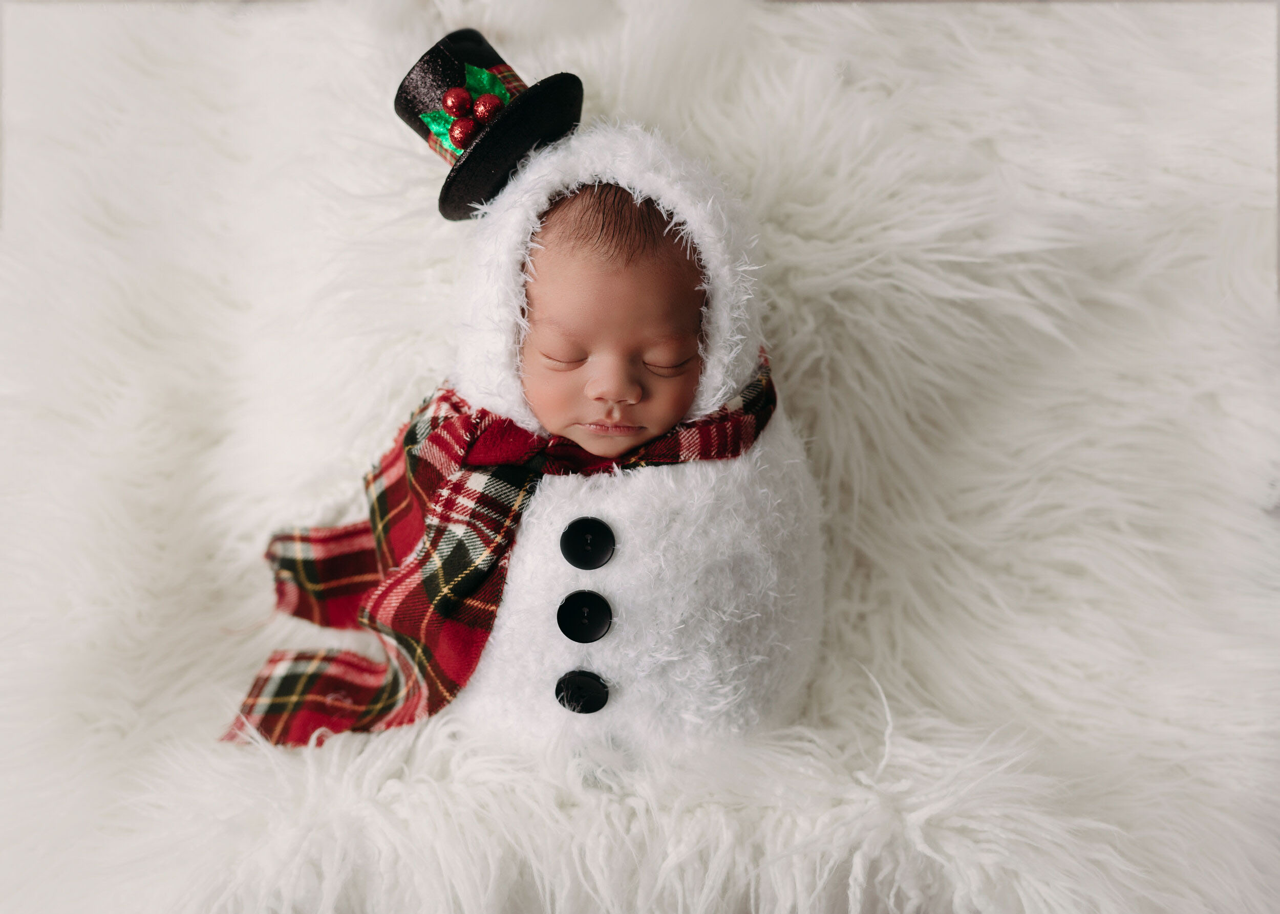 baby boy in snowman romper on flokati for christmas newborn session in minneapolis mn