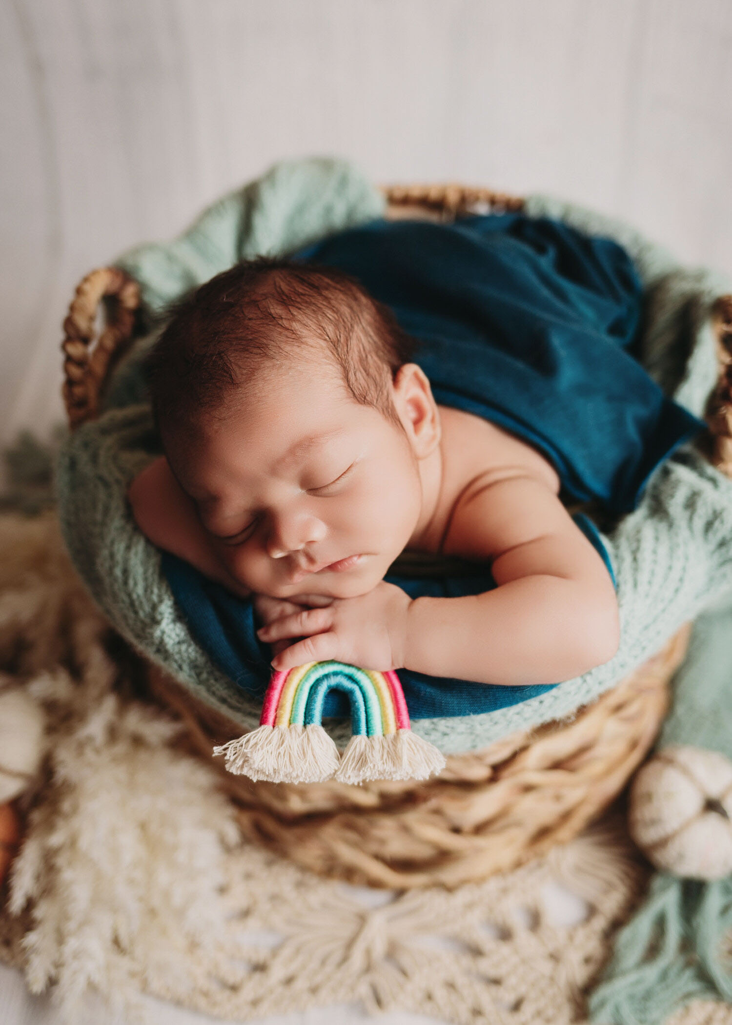 rainbow baby boy in blues and boho basket in newborn session for minneapolis photographer