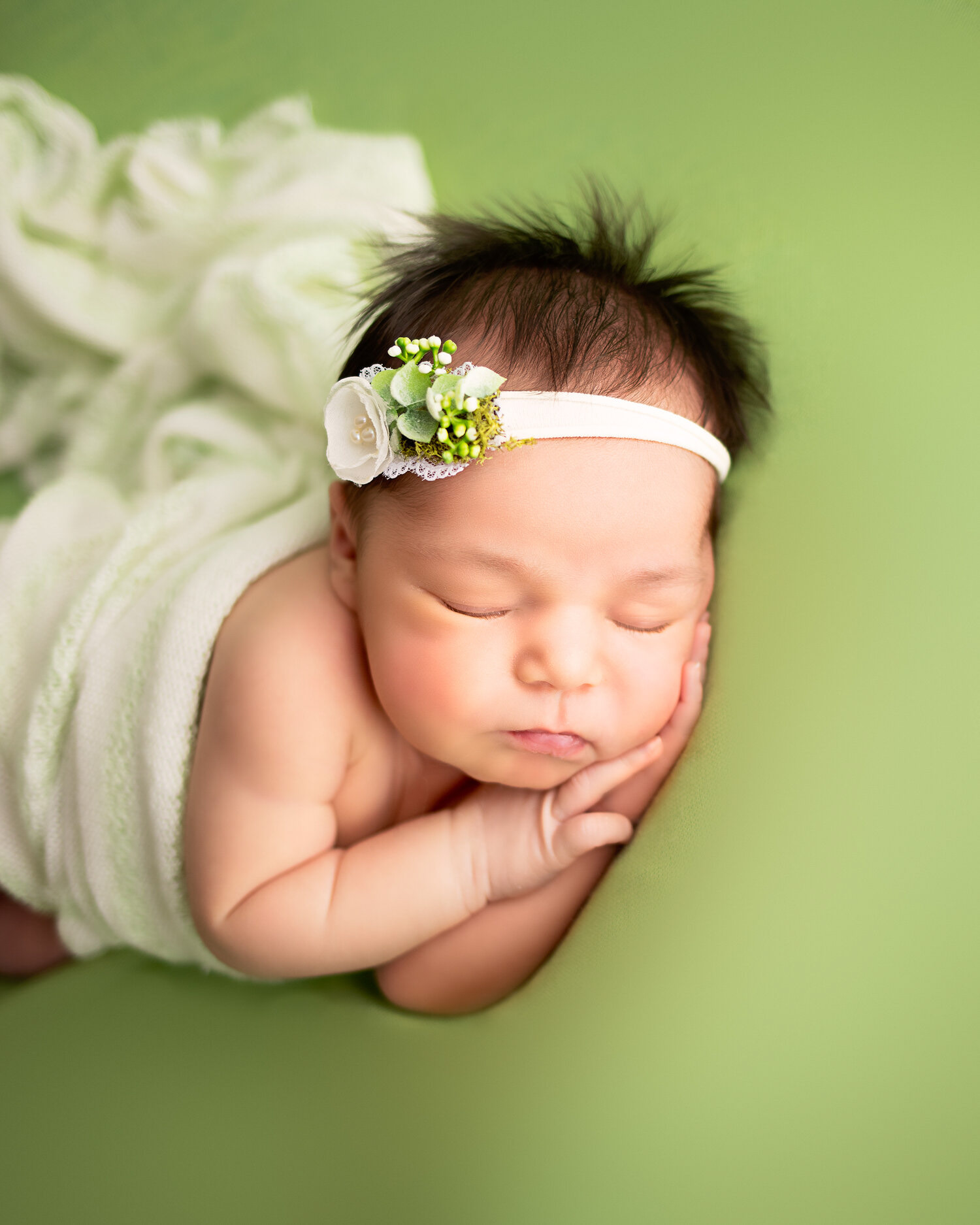 baby girl on green backdrop with white floral headband in side lay minneapolis newborn photoraphy