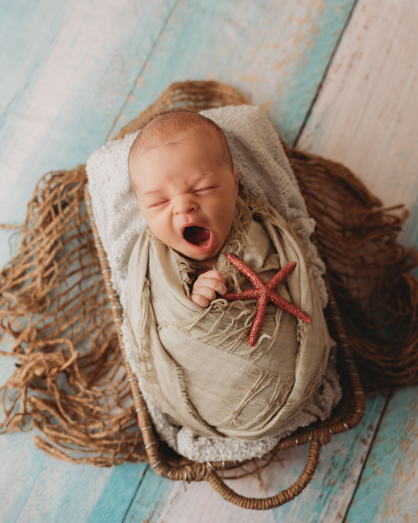 yawning baby boy on blue with starfish for newborn photography session in minneapolis mn
