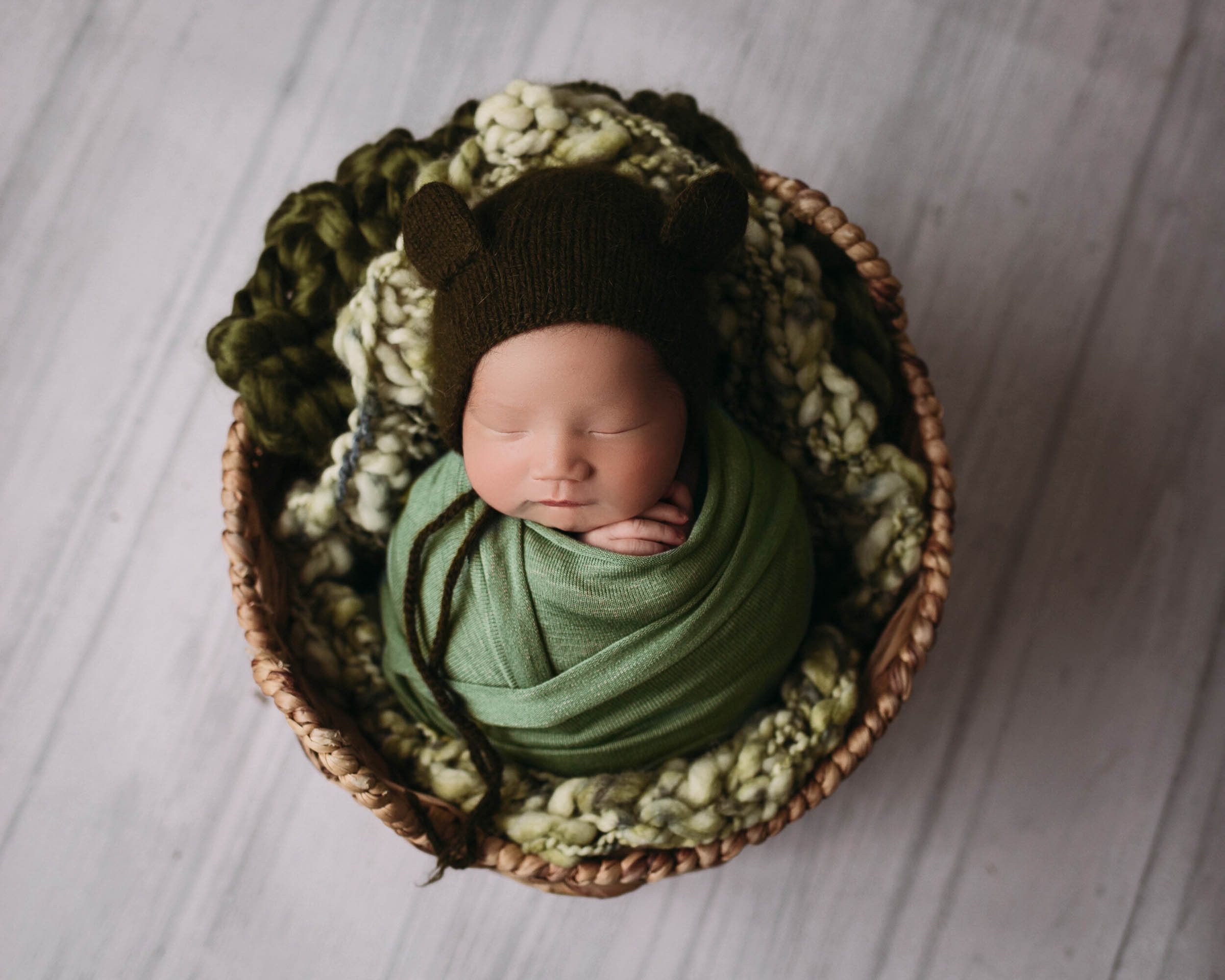 baby boy in greens and bear bonnet for newborn photographer in minneapolis mn