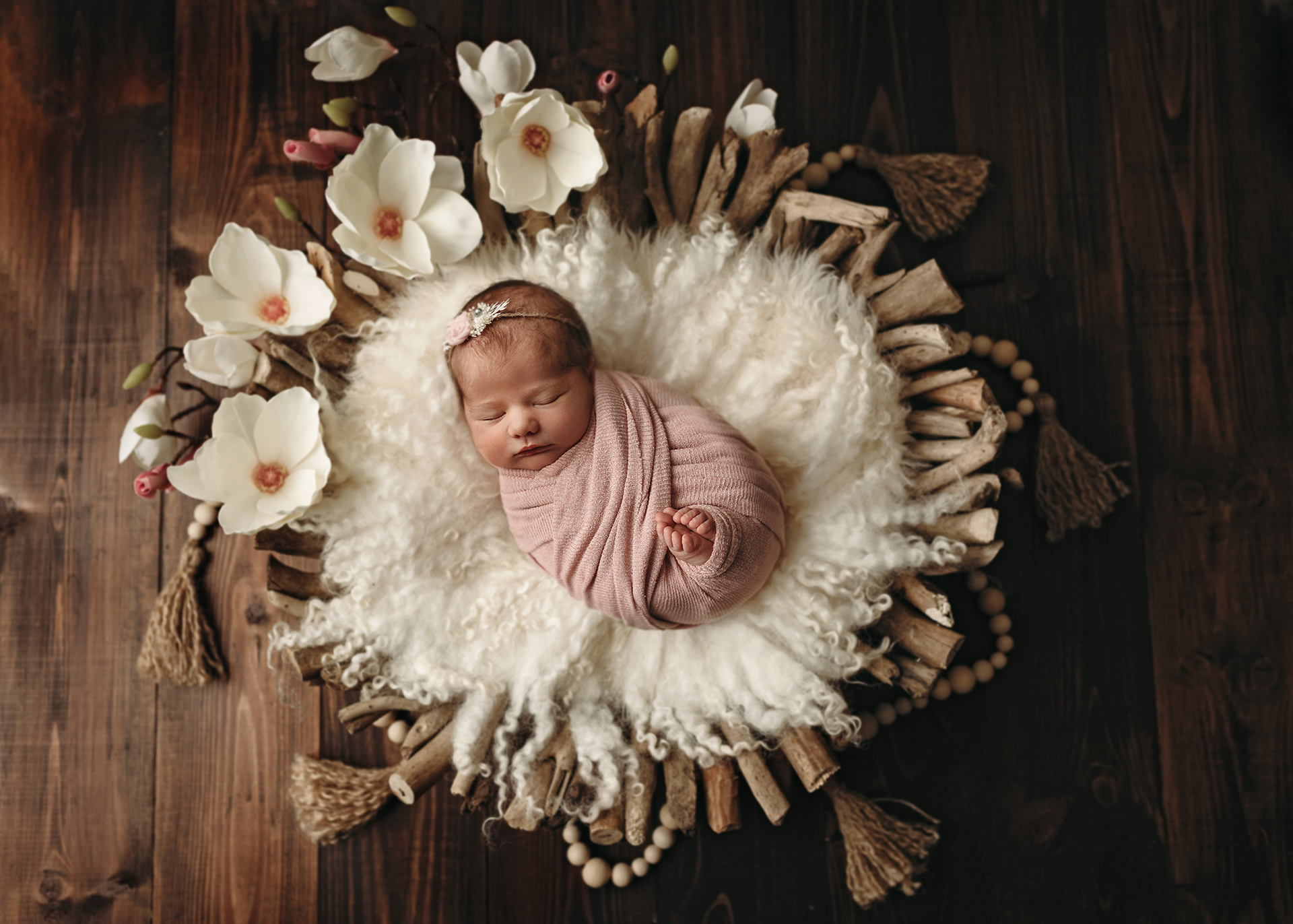 newborn girl in driftwood bowl with magnolias and tassels in minneapolis newborn session