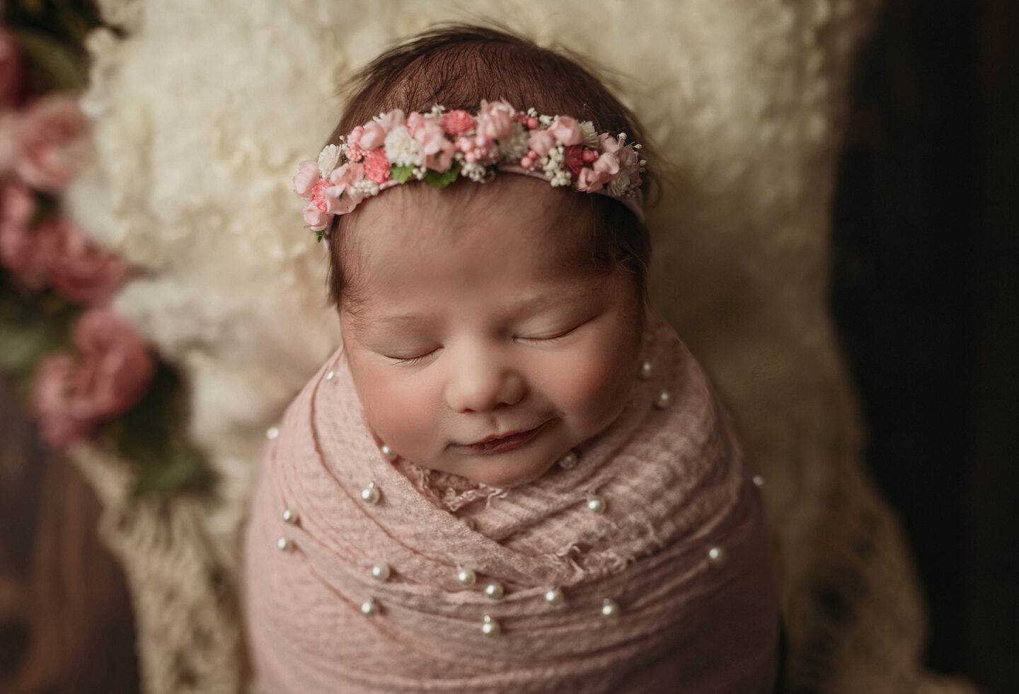 smiling newborn girl in pink pearls and flowers for newborn photography in minneapolis