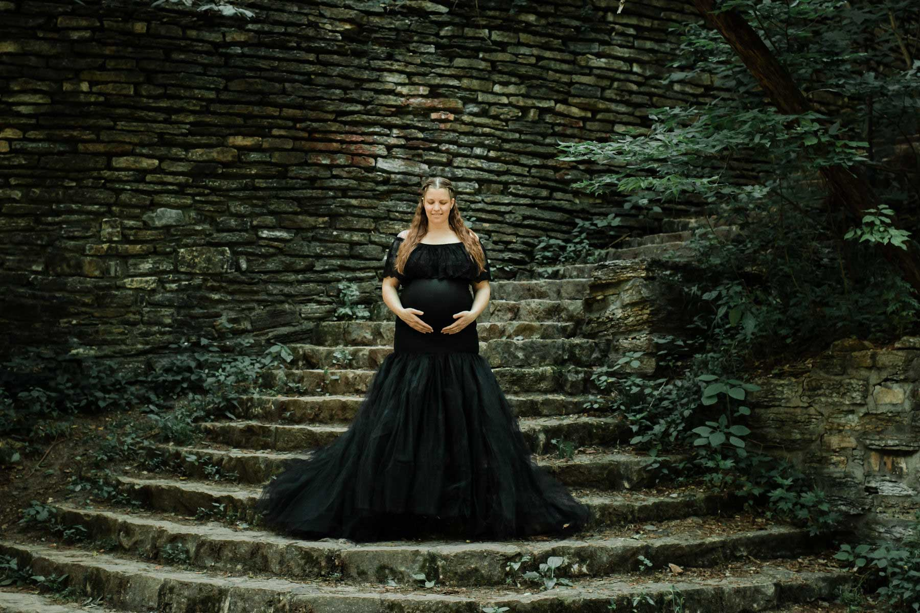 maternity photography session in black tulle gown on moss covered stairway minneapolis maternity studio