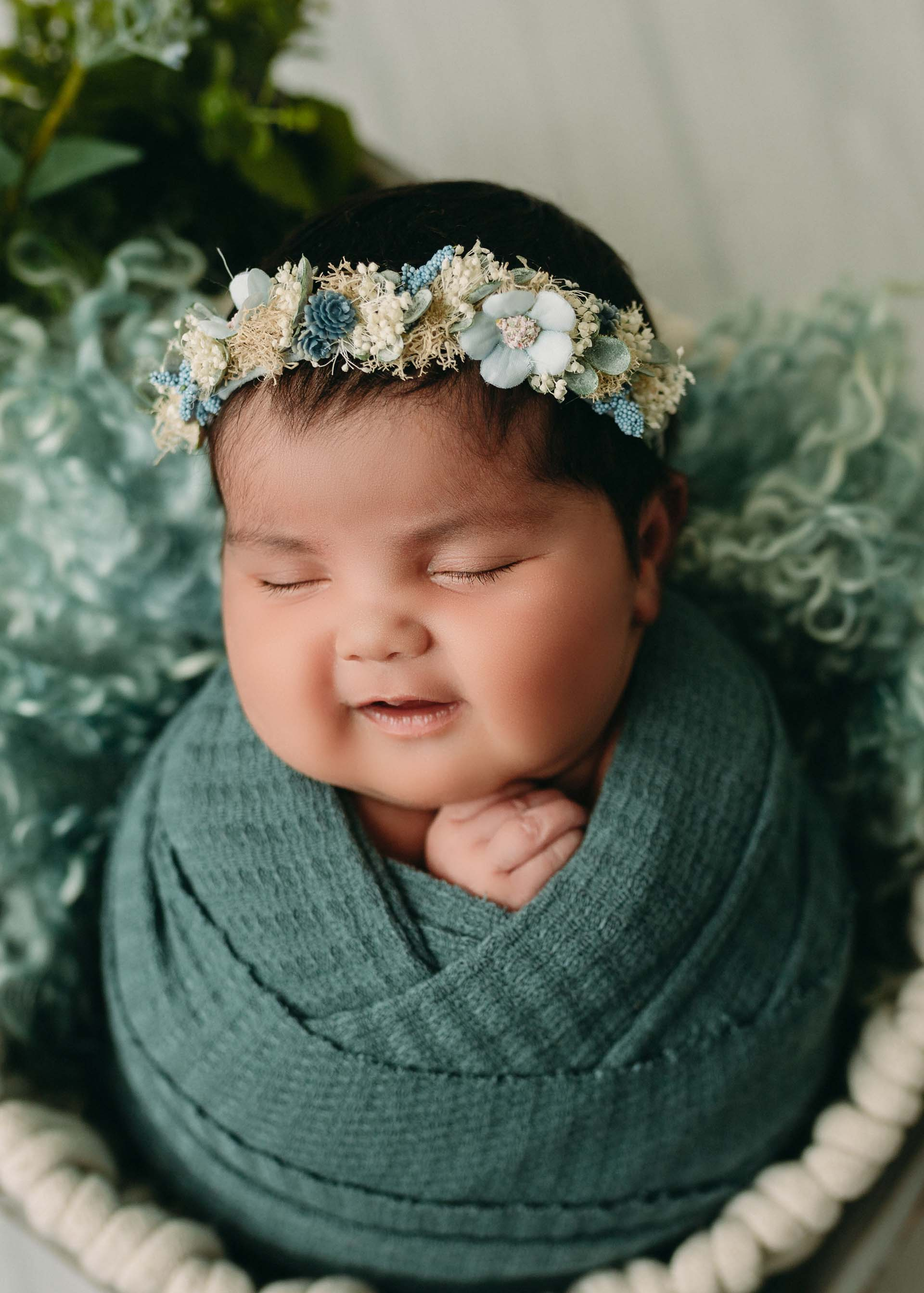 baby girl wrapped in teal with floral crown for minneapolis newborn photography session